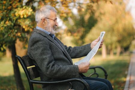Bearded elderly man in glasses reading newspaper in the autumn park. Handsome gray-haired man sitting on the bench early in the morning 免版税图像