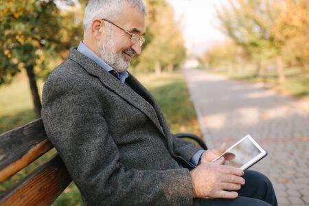 Mock up of senior man using tablet outside. Back view of elderly man sitting on the bench and using tablet