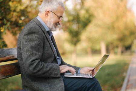 Elderly man use laptop in the park. Handsome senior man in glasses work outside 免版税图像