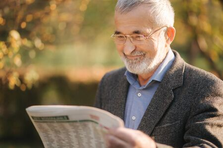 Senior man read a newspaper in the park. Background of yellow tree in autumn 免版税图像