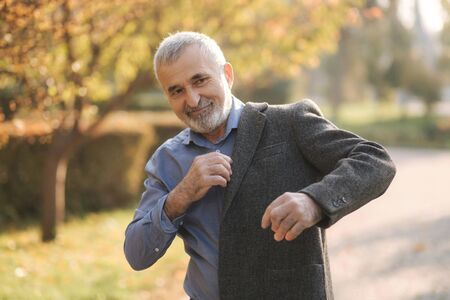 Handsome elderly man putting on a gray jacket. Old gray-haired bearded man walk in the autumn park. Yellow background 免版税图像