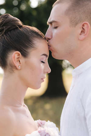 Close up portrait of groom kiss bride in forehead in front of big tree. Side view Foto de archivo