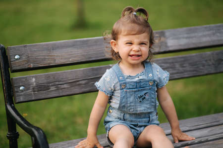 Adorable little girl laughing. Beautiful female kid in denim sitting on the bench in park. Happy little girl smile. Eighteen month