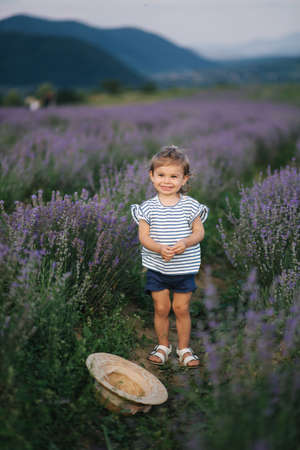 Adorable little girl walking in lavender field after sunset. Blue or purple lavender. Happy kid smile, run and jump.