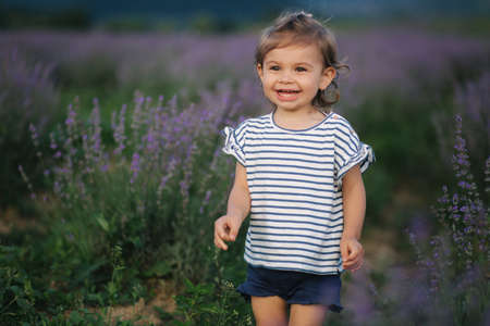 Portrait of adorable little girl walking in lavender field after sunset. Blue or purple lavender. Happy kid smile, run and jump. 免版税图像