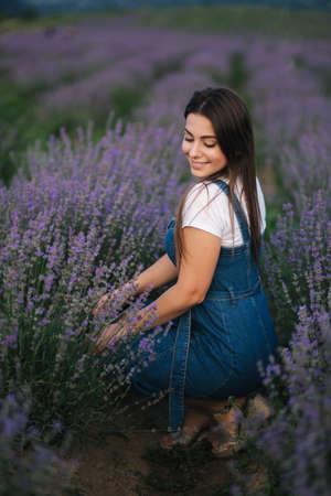 Young woman in denim dress sitting in lavender field in summer. Beautiful girl smile Foto de archivo