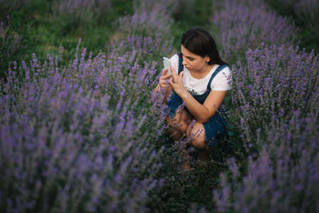 Young woman in denim dress sitting in lavender field in summer. Beautiful girl smile and make photo