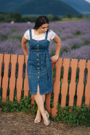 Attractive young woman walking in summer lavender field. Model dressed in denim sundress