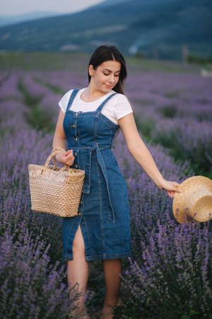 Attractive young woman walking in summer lavender field. Model dressed in denim sundress with straw hat and bag Foto de archivo