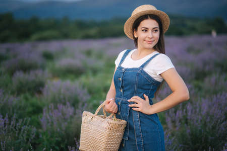 Portrait of attractive woman in lavender field in straw hat and denim sundress. Farm style in lavender with straw bag
