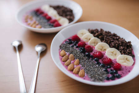 Smoothie bowl with fresh raspberry, blueberry, chia seeds, almonds, banana, and chocolate flakes. Morning breakfast on wooden table. Two ptales fith smoothie bows