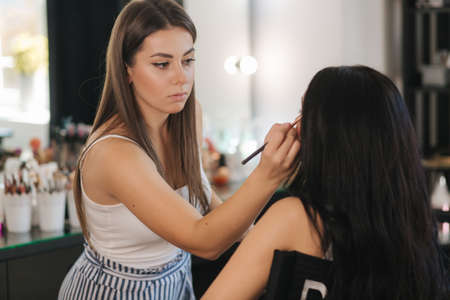 Makeup artist work in her beauty studio. Portrait of Woman applying makeup. Professional make up master. Beautiful make up artist start making a makeup for brunette woman