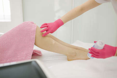 Young woman beautician in mask applies contact gel on the leg of a woman for laser hair removal in medical clinic. Close up. Pink glowes