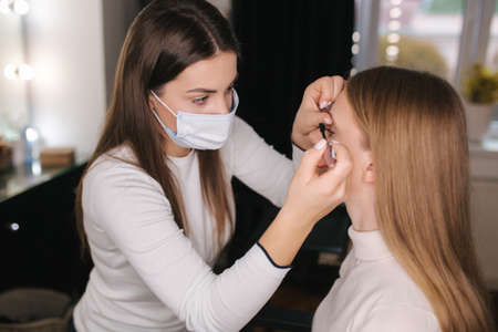 Female makeup artist working in beauty salon during quarantine. Make up artist in medical mask. Beautiful blond hair model 版權商用圖片