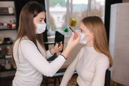 Female makeup artist working in beauty salon during quarantine. Make up artist in medical mask. Beautiful blond hair model in protective mask