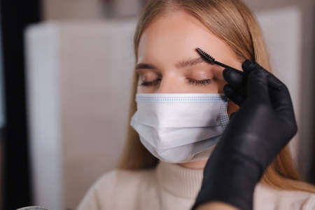 Brow and makeup master in protective mask gives shape to pull out with forceps previously painted with henna eyebrows in a beauty salon. Beautiful blond hair model in medical mask 版權商用圖片
