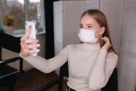Young woman make selfie in protective mask in beauty salon. Attractive girl sitting on high chair. Medical mask 版權商用圖片