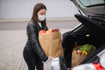 Groceries in females hand by the car truck. Woman in protective mask and disposable gloves. Fresh fruits in eco paket. Food shopping during coronavirus Covid-19 quarantine
