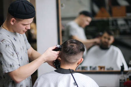 Handsome man getting haircut by barber while sitting in chair at barbershop.