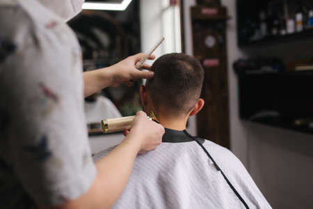 Professional hairdresser uses a hair clipper for fringing hair for a handsome bearder man. Barbershop