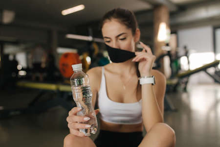 Attractive brunette female have a break in gym. Woman in protective mask. Woman take off mask to dring a water while sitting on the floor Stock Photo