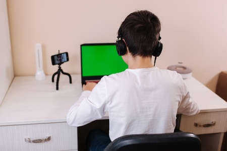 Back view of young boy play gamer on laptop greenscreen. Steamer in earphones capture video on his phone on tripod