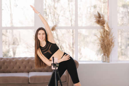 Young athletic woman blogger in balck sportswear shoots video on phone as she does exercises at home in living room. Sport and recreation concept. Fitness vlogger recording live tutorial video