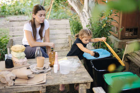 Young mom with her little daughter preparing for recycling different kind of rubbish and putting them into special containers. Different colours of trash bin. Caring about nature