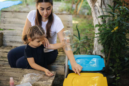 Caring about nature. Young mom with her little daughter preparing for recycling different kind of rubbish and putting them into special containers. Different colours of trash bin Standard-Bild
