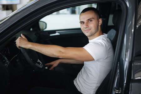 Man sitting in his new car in car showroom. Portrait of handsome man in car Standard-Bild