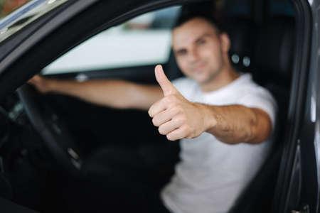 Man sitting in his new car in car showroom. Portrait of handsome man in car. Man defocused