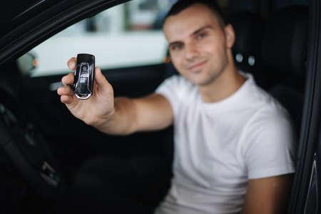 Man sitting in his new car in car showroom. Portrait of handsome man in car hold keys in hands. Keys in focus Standard-Bild