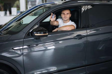 Man sitting in his new car in car showroom. Portrait of handsome man in car hold keys in hands