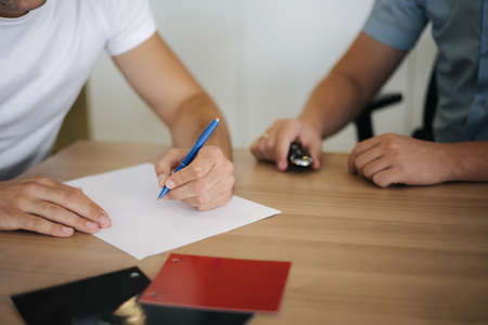 Man choosing and buying car at car showroom. Car salesman helps them to make right decision. Man sign documents