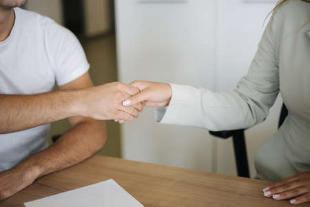 Close up of salesman and customer shake hands after successful sale in car showroom