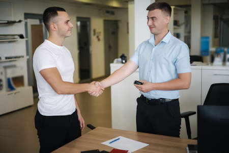 Men shake hands after successful sale in car showroom Standard-Bild