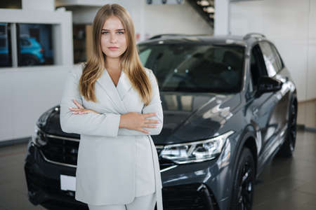 Portrait of salesperson in car showroom. Attractive young woman stend in front of car
