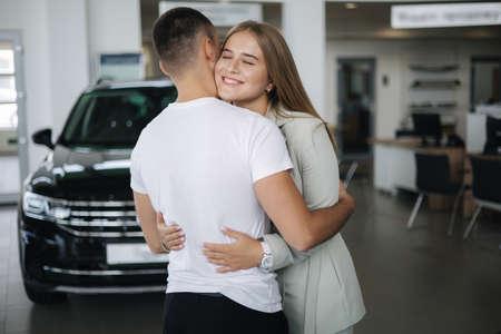 Happy woman hug his husband afrer buying car in car showroom. Man and woman buy new car