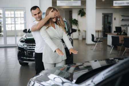 Man close eyes to his wife and makes a surprise buying car. Man and woman in car showroom