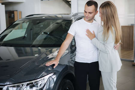Portrait of beautiful young couple happy after buying new car from car showroom. Woman hus her man and glad