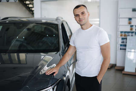 Portrait of handsome man standing by car in car shoowroom. Man buying new car Standard-Bild