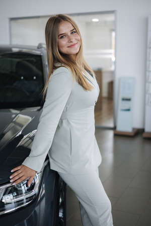 Portrait of gorgeous woman in showroom. Beautiful salesperson standing by car. Blond hair female after buying car Standard-Bild