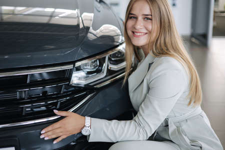 Business woman chossing a new car in a car showroom. Happy female hug new car and very glad Standard-Bild