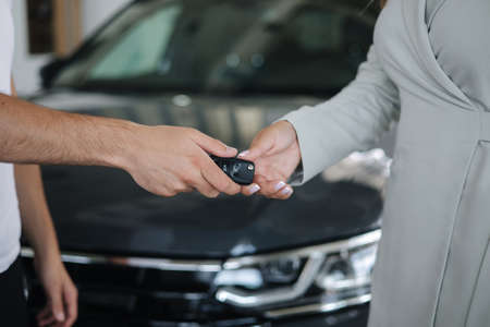 Salesman give keys from new to woman. Close-up of hands in front of car