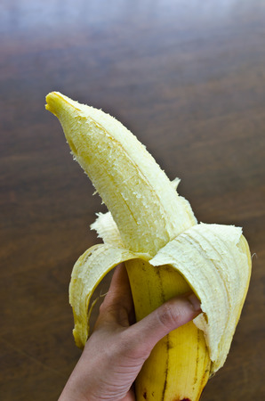 a large peeled-off banana in a hand  photo