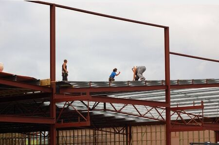 roof framework: roofers working on commercial building