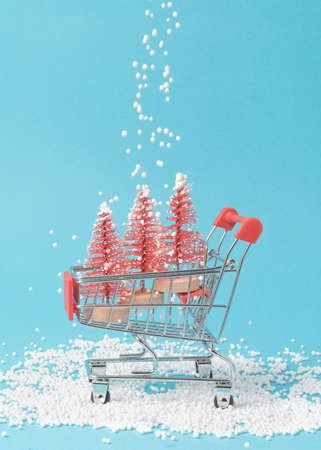 Creative composition of three red Christmas trees in shopping cart on pastel blue background with snow. Holiday shopping concept. 免版税图像