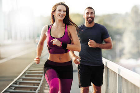 athletic wear: Happy couple running outdoors. People jogging together, living healthy lifestyle.