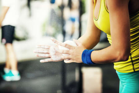 talc: Young fit woman is preparing hands with talc for crossfit training.