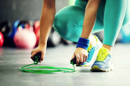 フィット若い女性が縄跳びを取っています。クローズ アップ。